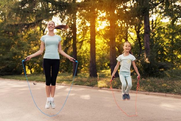 Niña y su madre saltando la cuerda en el camino en el parque Foto Premium