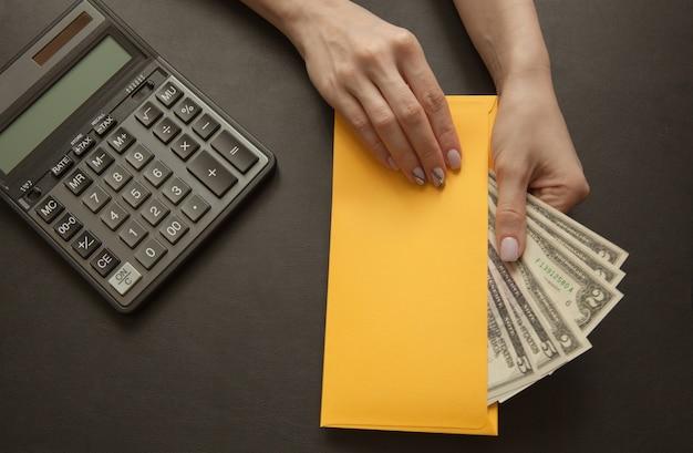 La niña en su mano sostiene un sobre amarillo con dinero. Foto Premium