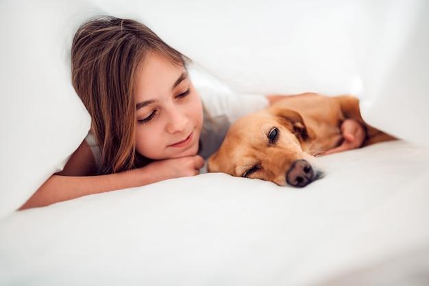 Niña y su perro acostado en la cama debajo de la manta Foto Premium