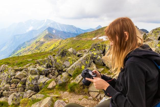 Niña en un suéter negro y polainas se encuentra en las montañas y fotografía la naturaleza de la belleza. Foto Premium