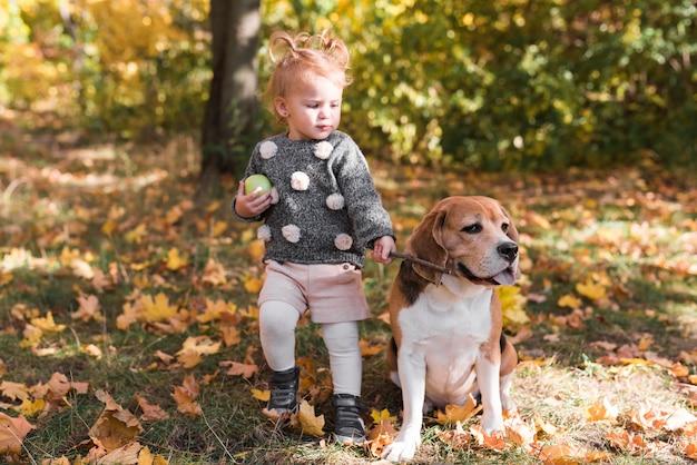 Niña, tenencia, perro, correa, en el estacionamiento Foto gratis