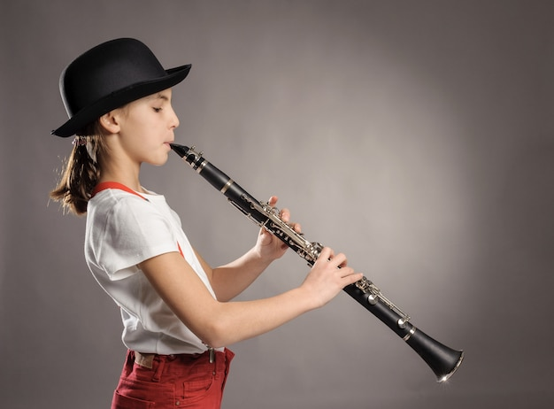 Niña tocando el clarinete en gris Foto Premium