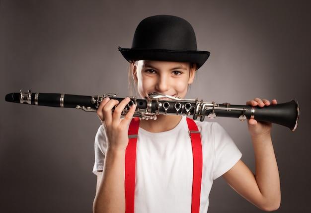 Niña tocando el clarinete sobre un fondo gris Foto Premium