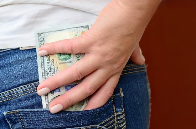 La niña toma muchos billetes de dólares del bolsillo trasero de los pantalones vaqueros. Foto Premium