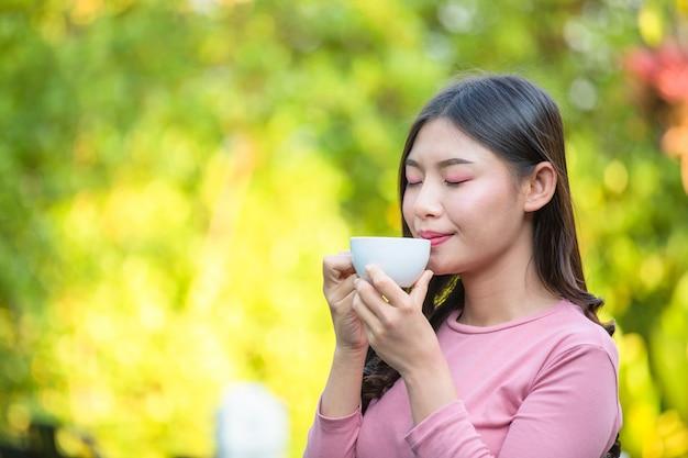 La niña está tomando café con placer en la cafetería. Foto gratis