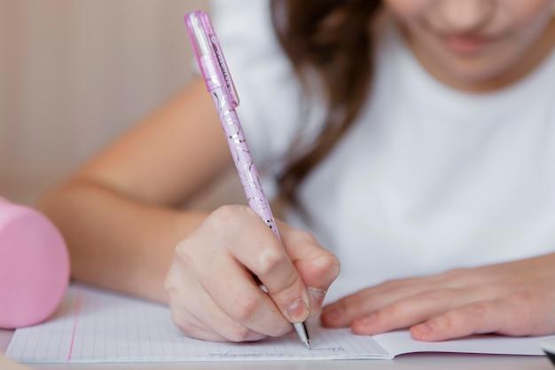 Niña tomando notas para una clase en línea Foto gratis