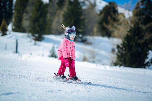 Niña en traje de esquí rosa esquiar en ladera cuesta abajo. actividad recreativa de deportes de invierno. Foto Premium