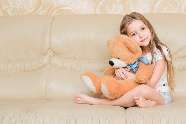 Niña tranquila abrazando oso de peluche Foto gratis