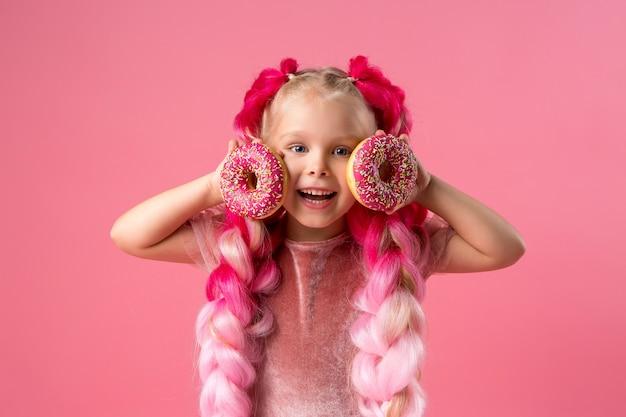 Niña con trenzas kanekalon con donas sobre fondo rosa Foto Premium