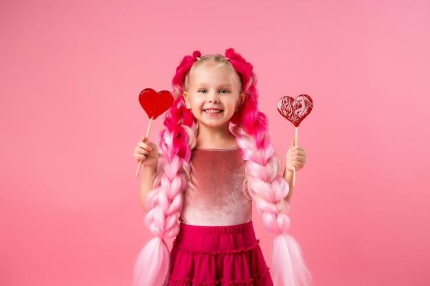 Niña con trenzas de kanekalon rosa sostiene una piruleta en forma de corazón sobre un fondo rosa Foto Premium
