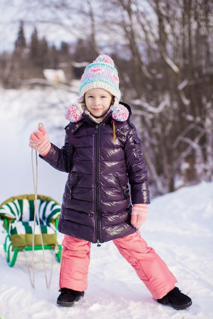 Niña va en trineo en un cálido día de invierno Foto Premium