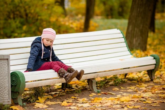 Niña triste niño solitario sentado en el banco en el parque Foto Premium