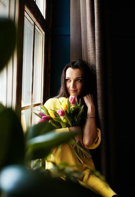 Una niña con tulipanes mira por la ventana. Foto gratis