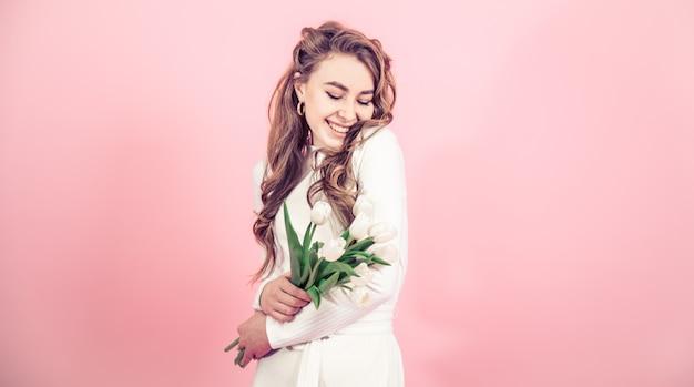Niña con tulipanes en una pared de color Foto gratis