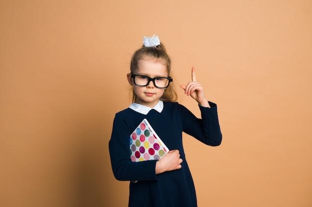 Niña en uniforme escolar con libro sobre fondo de color, mano, tener idea Foto Premium