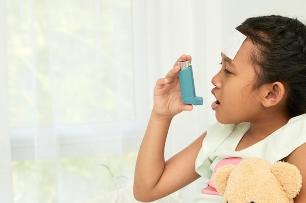 Niña usando inhalador para el asma Foto Premium