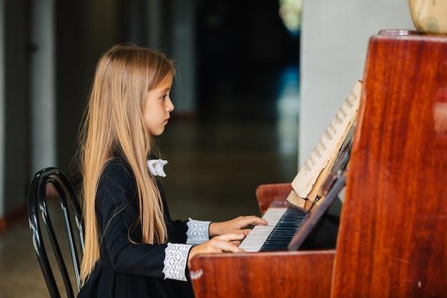 Niña vestida de negro aprende a tocar el piano. el niño toca un instrumento musical. Foto Premium