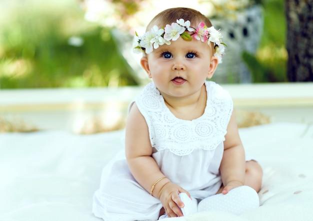 be7be9ce1 Niña con vestido blanco en un jardín de primavera con corona de flores