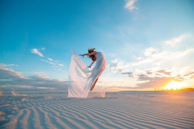 Una niña en un vestido blanco mosca baila y posa en el desierto de arena al atardecer Foto Premium