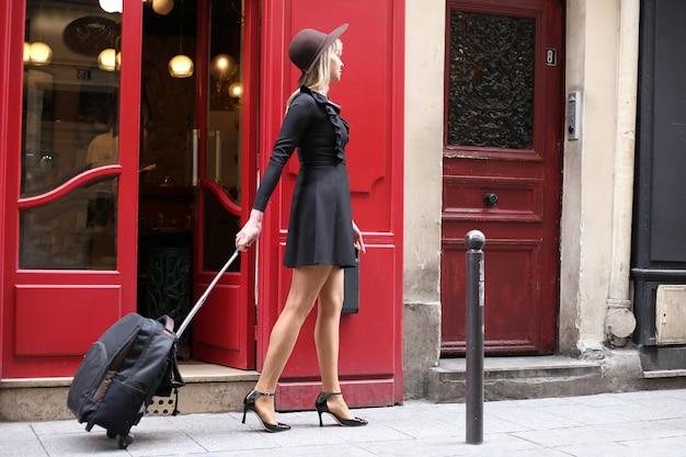 Una niña con un vestido negro corto con un sombrero y una maleta está caminando por la calle en parís Foto Premium