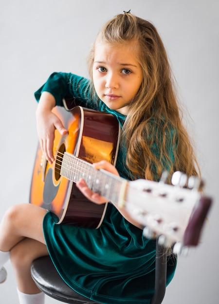 Niña en vestido tocando guitarra acústica Foto gratis