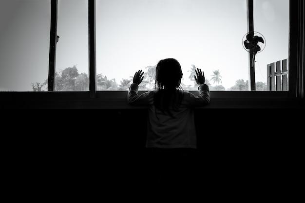 Las niñas asiáticas de niños están de pie en la oscuridad, mirando por la ventana, tristes Foto Premium