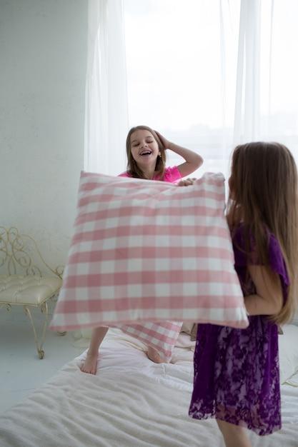 Niñas bonitas con vestidos de princesa rosa y morado tienen pelea de cojines Foto Premium