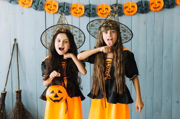 Niñas en disfraces de halloween que simulan suicidarse Foto gratis