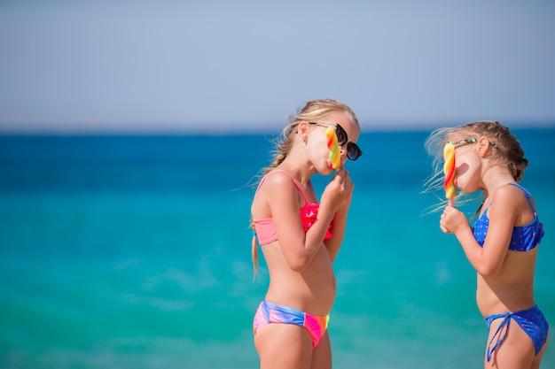 Niñas felices comiendo helado durante vacaciones en la playa. concepto de personas, niños, amigos y amistad Foto Premium