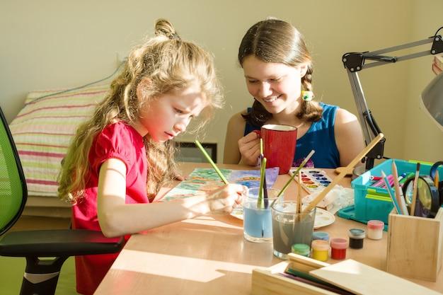 Niñas hermanas en casa en la mesa pintan con acuarela. Foto Premium