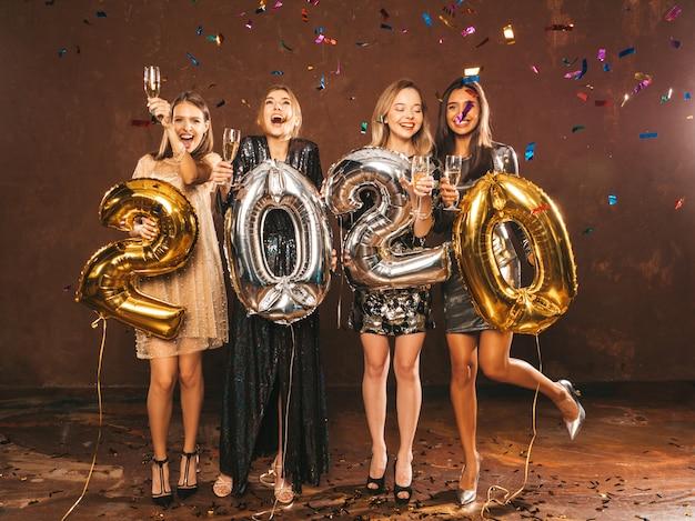 Niñas hermosas felices en elegantes vestidos de fiesta sexy con globos dorados y plateados 2020 Foto gratis