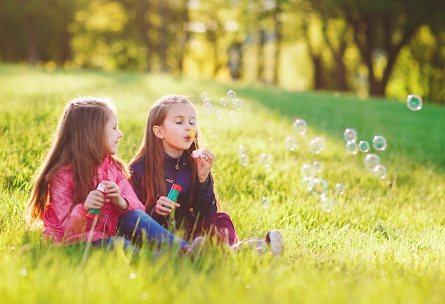 Las niñas juegan con pompas de jabón. Foto Premium