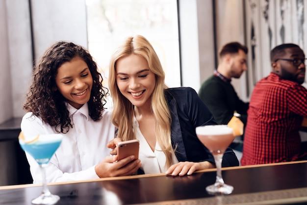 Las niñas miran la pantalla de un teléfono móvil. Foto Premium