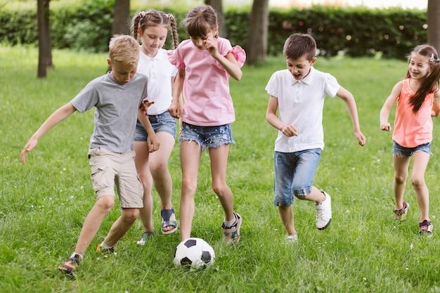 Niñas y niños jugando al fútbol Foto gratis
