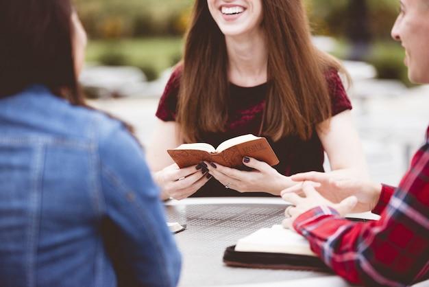 Niñas sentadas alrededor de una mesa y leyendo un libro con un fondo borroso Foto gratis