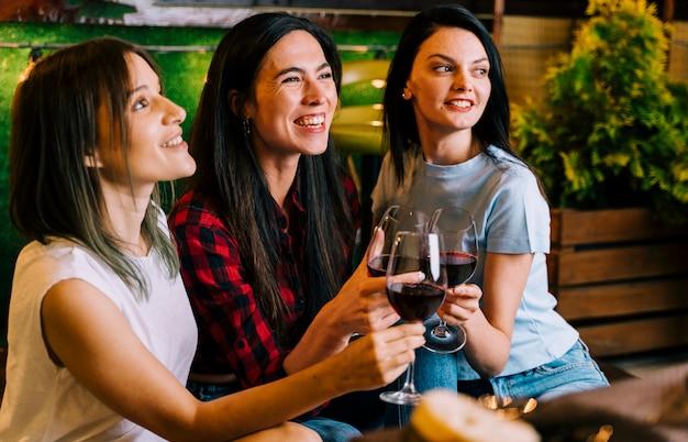 Niñas sonriendo al vino tostado en fiesta Foto gratis