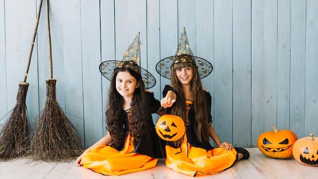 Niñas en trajes de bruja sentado en el piso sosteniendo la cesta de halloween y sonriendo Foto gratis