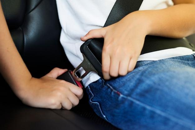 Niño abrochando su cinturón de seguridad Foto gratis