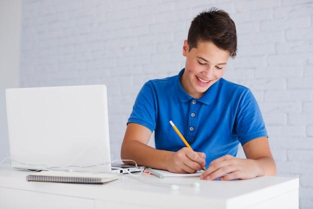 Niño adolescente haciendo la tarea | Foto Gratis