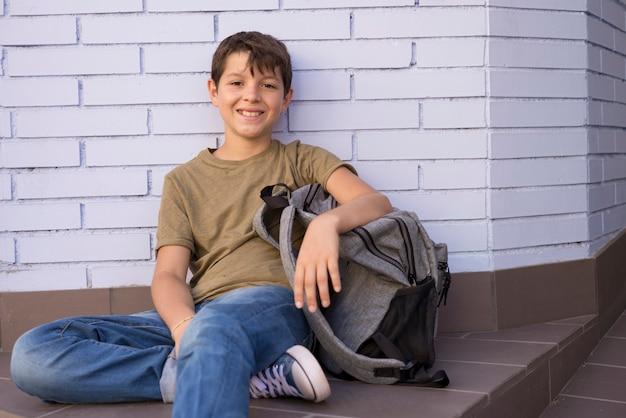 Niño alegre llevando su mochila Foto Premium