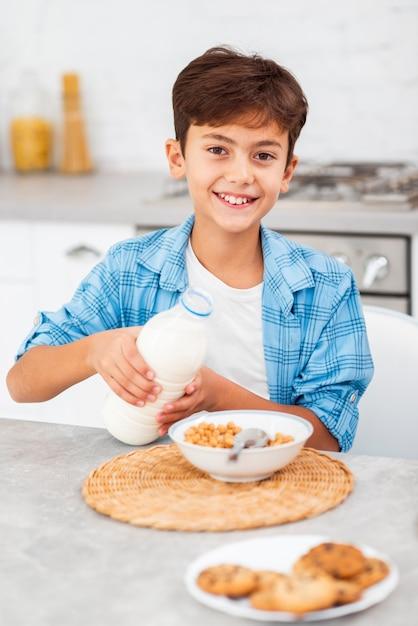 Niño de alto ángulo vertiendo leche sobre cereales Foto gratis