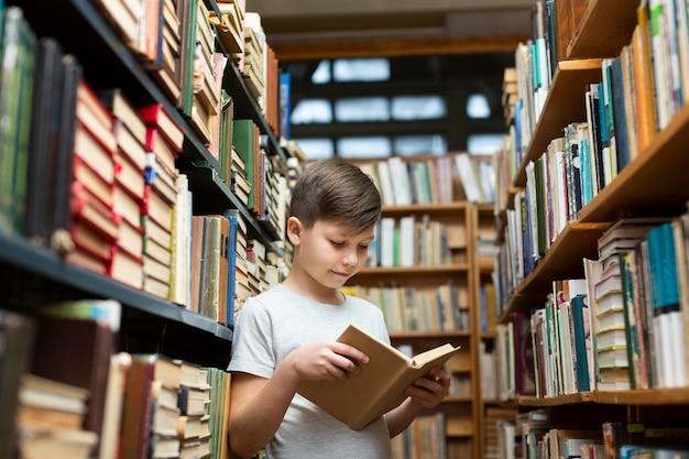 Niño de ángulo bajo en la lectura de la biblioteca Foto gratis
