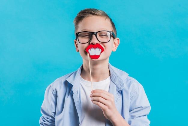 Un niño con anteojos negros que sostienen una sonrisa en frente de su boca contra un fondo azul Foto gratis