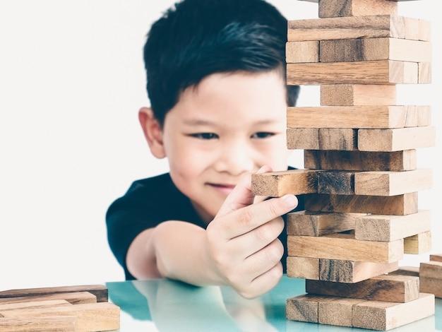 Un niño asiático está jugando al juego de la torre de bloques de madera para practicar habilidades físicas y mentales. Foto gratis