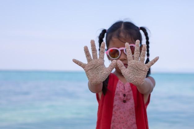 Niño asiático manos con arena divirtiéndose en la playa Foto Premium