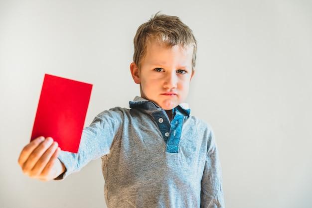 Niño asustado con tarjeta roja anti bullying. Foto Premium