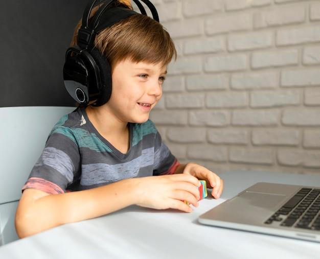 Niño con auriculares que asisten a la escuela virtual Foto gratis