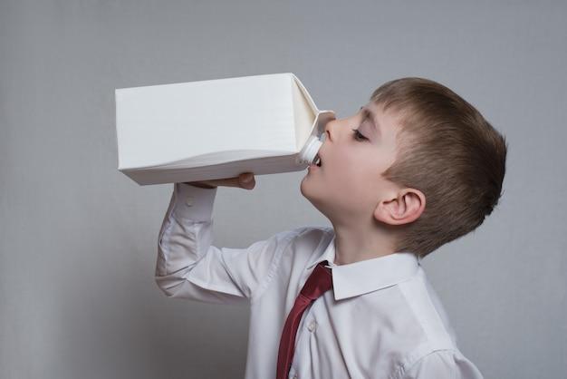 Niño bebe de un gran paquete blanco. Foto Premium