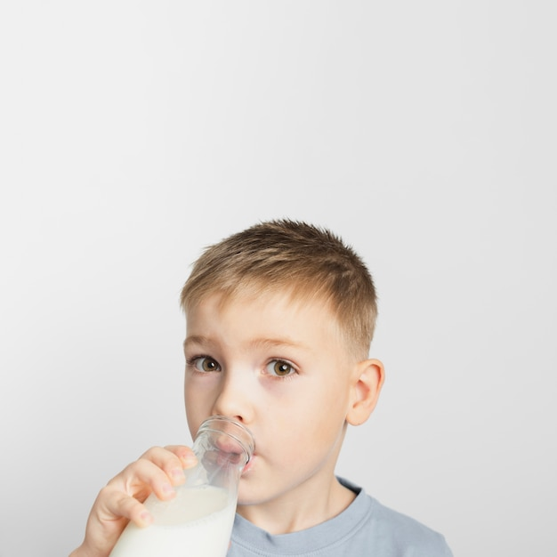Niño bebiendo leche de botella Foto gratis