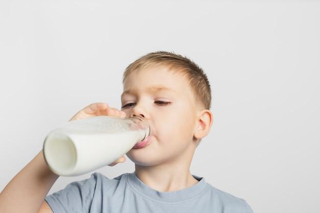 Niño bebiendo leche con botella Foto gratis